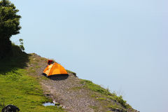Solitary orange tent camped near water edge Stock Photography
