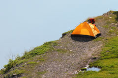 Solitary orange tent camped near water edge Royalty Free Stock Photos