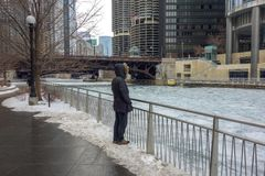 Person on Chicago riverwalk looking at icy river Royalty Free Stock Photos