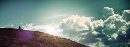 Solitary Person Sitting on Hill Watching Sunrise. Panoramic of Solitary Person Sitting Alone on Hill Watching Bright Sunrise in Cloudy Blue Sky - Concept Image Royalty Free Stock Photography