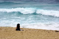 Solitary Person on Stormy Bronte Beach, Sydney, Australia. Heavy and churned up surf and large waves at Bronte Beach during stormy weather, with a solitary lone Royalty Free Stock Images