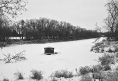 Portable fishing house on a river in the winter. A solitary portable fishing house rests on the ice of a snow covered river in the cold of winter stock photo