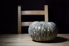 Solitary pumpkin on rustic table with chair. Royalty Free Stock Images