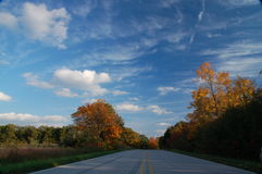 Solitary Road. Country road stretching through colored trees Stock Photography