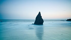Solitary rock at the beach stock images