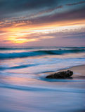 Solitary rock at sunset Stock Images