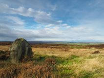 Solitary rock overlooking moors. Solitary rock with views over Howdale Moor with scenic sky in the North York Moors National Park, Yorkshire, UK Stock Photos