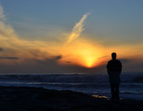 Solitary sunset. Silhouette of man watching the sunset Stock Photo