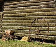 Wagon Wheel. A solitary wagon wheel leaning against a log cabin Royalty Free Stock Image