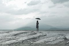 Solitary woman looks at infinity and uncontaminated nature on a stormy day Royalty Free Stock Photo