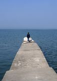 Solitary Woman on Pier. A lone woman standing at the end of a long cement pier Royalty Free Stock Image