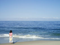 Solitary woman standing on sandy beach near water�s edge, looking at Pacific Ocean horizon, rear view Stock Photos