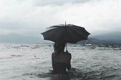 Solitary woman with umbrella waiting for the storm into the sea