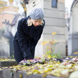 Solitary woman visiting relatives grave. Stock Photos