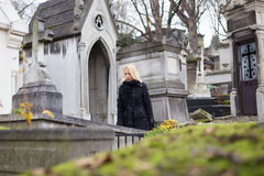 Solitary woman visiting relatives grave. Stock Images