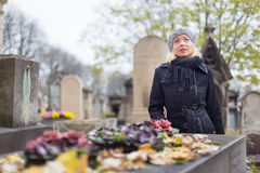 Solitary woman visiting relatives grave. Royalty Free Stock Photography