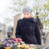 Solitary woman visiting relatives grave. Stock Photo
