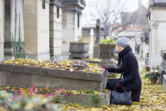 Solitary woman visiting relatives grave. Royalty Free Stock Photos