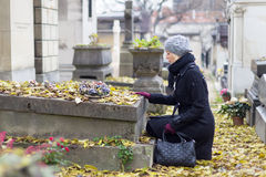 Solitary woman visiting relatives grave. Stock Image