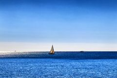 Solitary yacht out on a deep blue sea stock photography