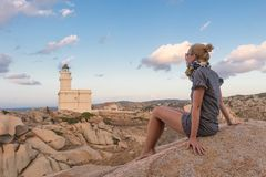 Solitary young female traveler watches a beautiful sunset over lighthouse and spectacular rock formations of Capo Testa Stock Photography