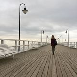 Solitary young woman walking on pier. Solitary young blond woman in black walking on deck of wooden pier in Gdynia, Poland, gray sky Royalty Free Stock Images