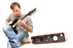 Solitt kort och gitarrist som spelar musik Fotografering för Bildbyråer