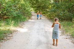 Solitude. Three kids having walk in the wood. One is apart of other Royalty Free Stock Image