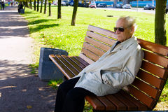 Solitude. Portrait of the old man sitting alone on the bench Royalty Free Stock Photo