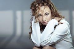 Solitude. Sad Latin lady with curly hairs sitting indoors. Horizontal photo Stock Image
