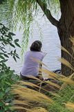 Solitude. Young woman sitting in a secluded area on the waters edge, reading a book Stock Photos