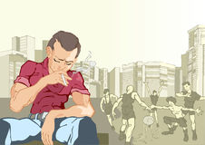 Solitude. A young man sits and smokes a cigarette.Behind him a bunch of friends playing football Stock Photo