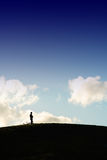 Solitude. A silhouette man standing on top of the hill Royalty Free Stock Image
