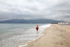 Solitude. Red dressed caucasian women walking at a beach Asprovalta Greece Stock Photo