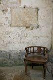 Solitude. A wooden chair under an old wall inscription in a corner of an old cathedral Stock Photos