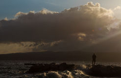 Solitude. Man standing on the shore at dusk Stock Images