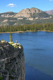 Solitude. Hiker on the top of cliff with lake and mountains Stock Image
