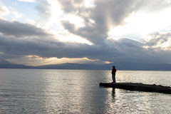 Solitude. Silhouette of man standing on a peer by the sea Stock Photography