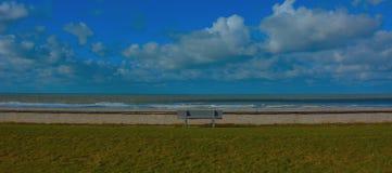 Solitude, banc abandonné sur une pelouse avec vue sur la Mer du Nord Photos stock