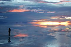 Solitude on the bolivian saltflats. Watching the sunset in solitude over the Bolivian saltflats Stock Photo