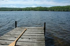 Solitude - cedar dock on a small calm lake. Canoe paddle on a wooden dock on a calm lake solitude water pier travel nature blue landscape background sky old royalty free stock photos