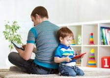 Solitude de l'enfant et du père jouant avec le comprimé image stock