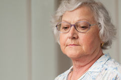 Solitude and depression. Senior aged woman looking down with sadness, indoor closeup shot Royalty Free Stock Photography