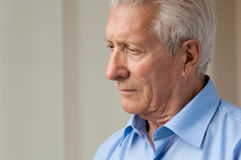 Solitude and depression. Sad senior man looking down with anxiety Stock Image