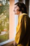 Solitude - femme supérieure regardant par l'hublot Photographie stock
