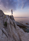 Solitude girl watching sunset high up on cliff by sea Stock Photography
