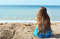Solitude near the sea. Young longhaired woman sitting alone at the beach Stock Photography