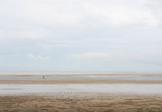 Solitude person walks down the seaside Stock Photography