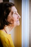 Solitude - senior woman looking through window. Solitude concept  - sad 80s senior woman looking through window at home Royalty Free Stock Image