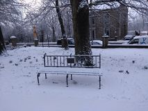 Solitude. A snow-covered bench in winter, park royalty free stock images
